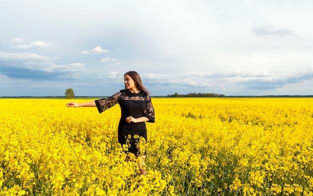 Reizendes braunhaariges mädchen mit dem langen haar im schwarzen kleid steht auf dem gelben gebiet. konzept von sommer, jugend, freiheit. platz für text.