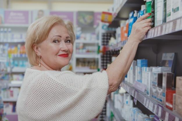 Reizendes einkaufen der älteren frau an der drogerie