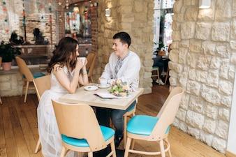 Reizendes junges Hochzeitspaar sitzt an einem Abendtische in einem gemütlichen Café