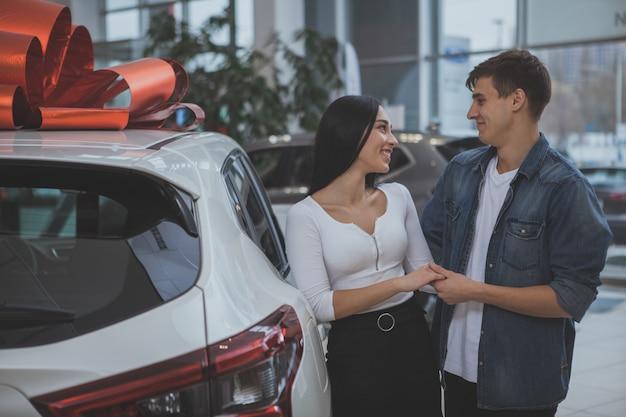 Reizendes junges verheiratetes paar, das zusammen neuwagen kauft