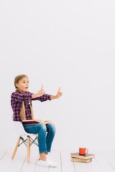 Reizendes kleines mädchen, das auf einem stuhl sitzt, ein buch lesend
