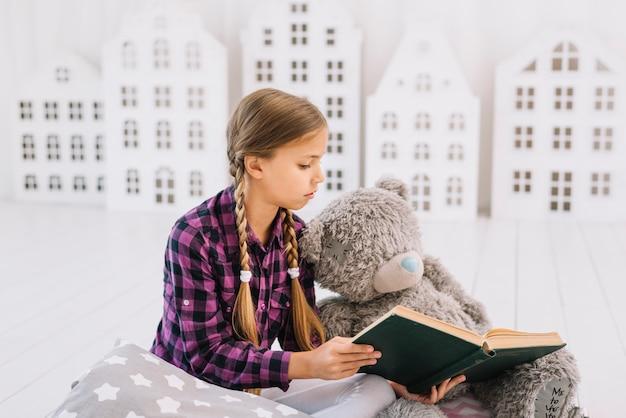 Reizendes kleines mädchen, das ein buch mit ihrem teddybären liest