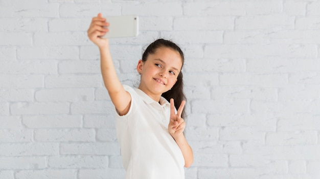 Reizendes kleines mädchen, das ein selfie nimmt