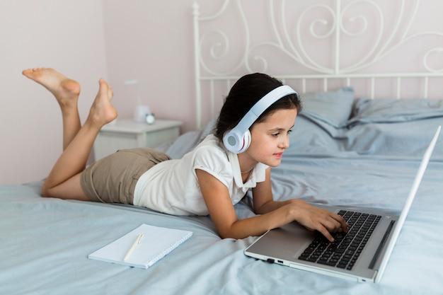 Reizendes kleines mädchen, das ihren laptop verwendet