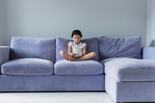 Reizendes kleines mädchen mit smartphone auf dem sofa