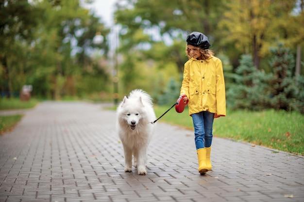 Reizendes mädchen auf einem weg mit einem schönen hund in einem park im freien