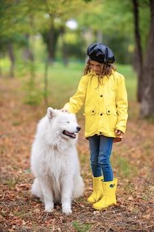Reizendes mädchen in den gelben gummistiefeln und im regenmantel auf wege, spielt mit einem schönen weißen samoyedhund im herbstpark