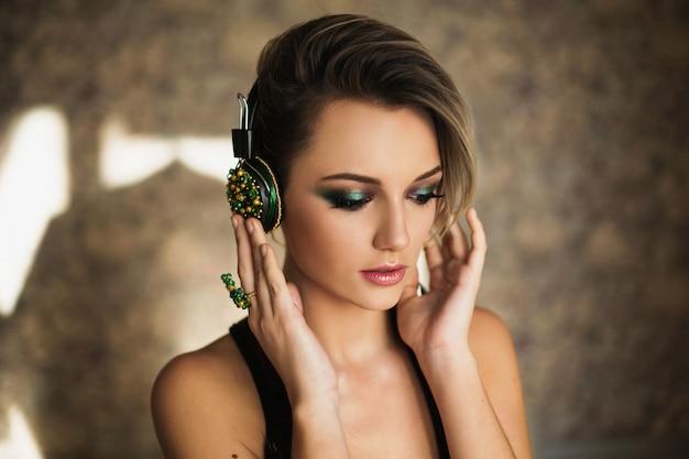 Reizendes mädchen mit gebräunter haut und dem weißen haar hörend musik auf kopfhörern. weibliches schönheitsporträt eines schönen make-up. gute musik genießen
