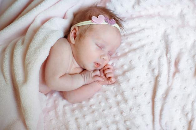 Reizendes neugeborenes mädchen, das auf rosa decke mit platz für ihren text schläft