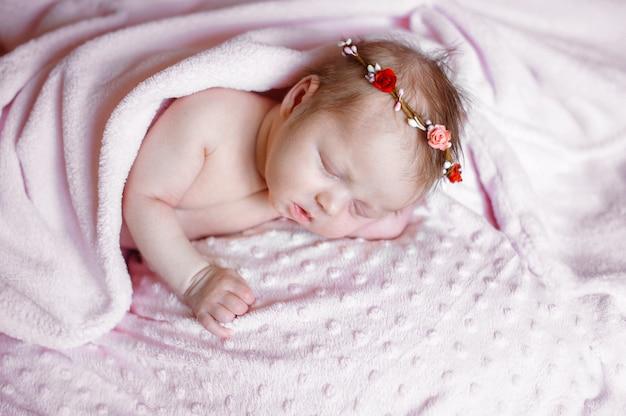 Reizendes neugeborenes mädchen, das auf rosa decke schläft