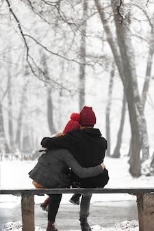 Reizendes paar, das mit einer umarmung sich wärmt