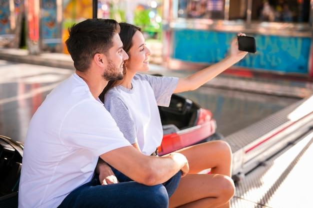 Reizendes paar, das selfie an der messe nimmt