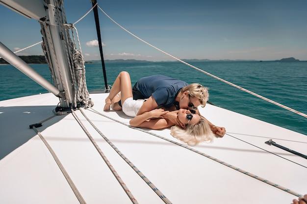 Reizendes paar mann und frau in der sonnenbrille, die auf einer weißen yacht liegt.