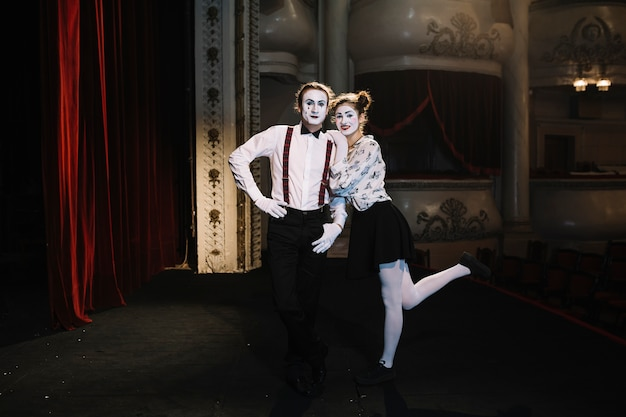 Reizendes porträt des weiblichen und männlichen pantomimekünstlers, der auf stadium steht