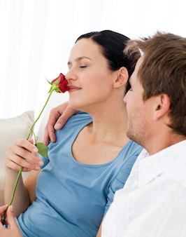 Reizendes wwoman, das eine rose sitzt auf dem sofa riecht