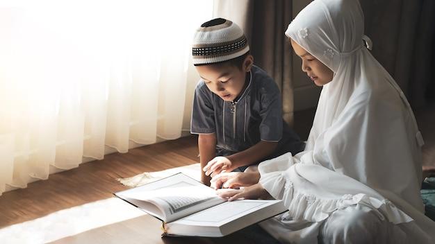 Religiöse asiatische muslimische kinder lernen den koran und studieren den islam, nachdem sie zu hause zu gott gebetet haben. sonnenuntergangslicht scheint durch das fenster. friedliches und wunderbar warmes klima.