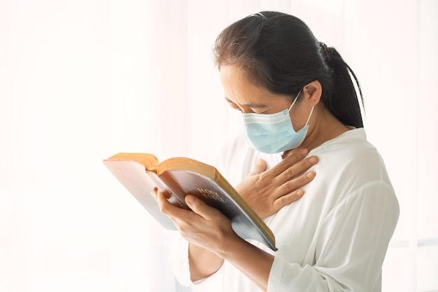 Religiöse frau in schützender gesichtsmaske und betend zu gott um hilfe zu hause. mädchen christliches gebet in medizinischer gesichtsmaske. coronavirus (covid-19