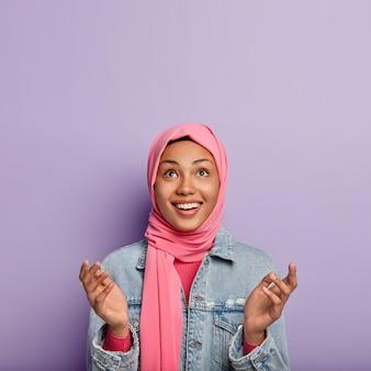 Religiöse fröhliche frau hat islamische ansichten, hebt handflächen, betet und schaut hoffentlich nach oben
