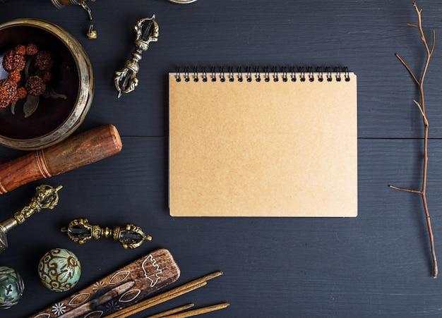 Religiöse musikinstrumente für meditation und alternativmedizin, leeres notizbuch mit braunen blättern
