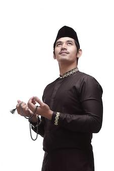 Religiöser asiatischer moslemischer mann im trachtenkleid betend