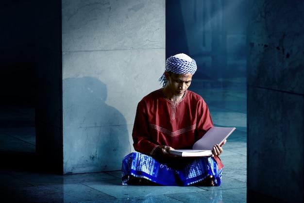 Religiöser moslemischer mann, der heiligen koran liest
