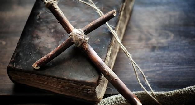 Religiöses altes buch auf einem holztisch. ein religiöses kreuz mit einem seil und sackleinen neben der bibel gebunden. anbetung, sünden und gebet.