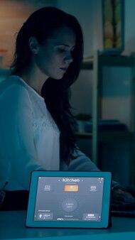 Remote-frau, die in einem modernen haus arbeitet und dem tablet sprachbefehle gibt