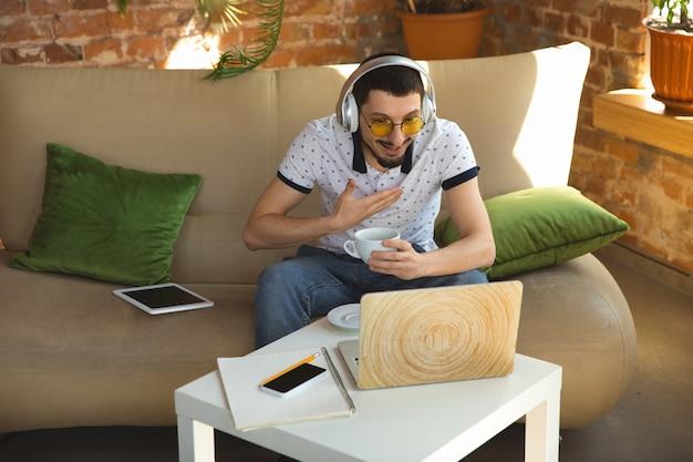 Remote-meeting. mann, der während der quarantäne von coronavirus oder covid-19 von zu hause aus arbeitet, remote-office-konzept. junger geschäftsmann, manager, der aufgaben mit smartphone, computer erledigt, hat online-konferenz.