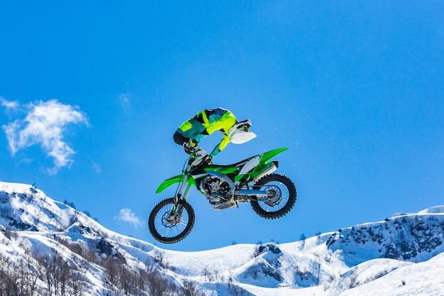 Rennfahrer auf einem motorrad im flug in den schneebedeckten bergen