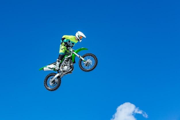 Rennfahrer auf einem motorrad im flug, springt und hebt auf einem sprungbrett gegen den blauen himmel ab