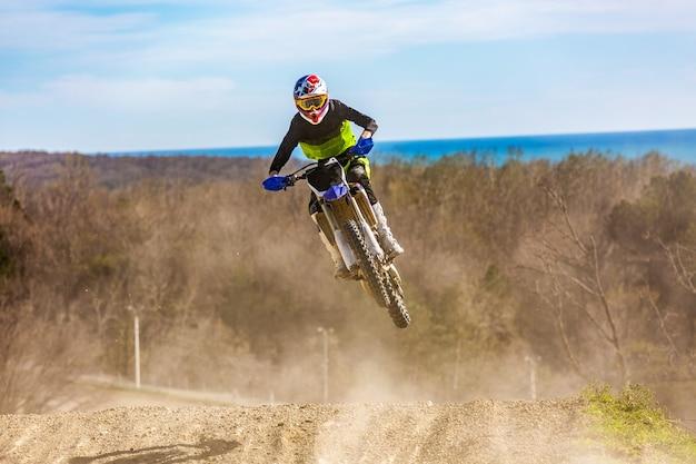 Rennfahrer auf einem motorrad im flug, springt und hebt auf einem sprungbrett gegen den himmel ab.