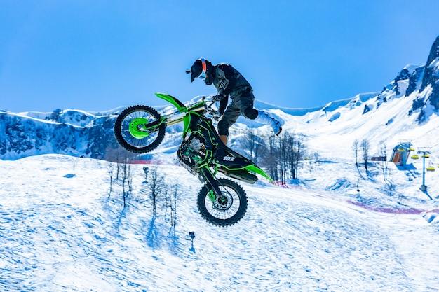 Rennfahrer auf einem motorrad im flug, springt und hebt auf einem sprungbrett gegen die schneebedeckten berge ab
