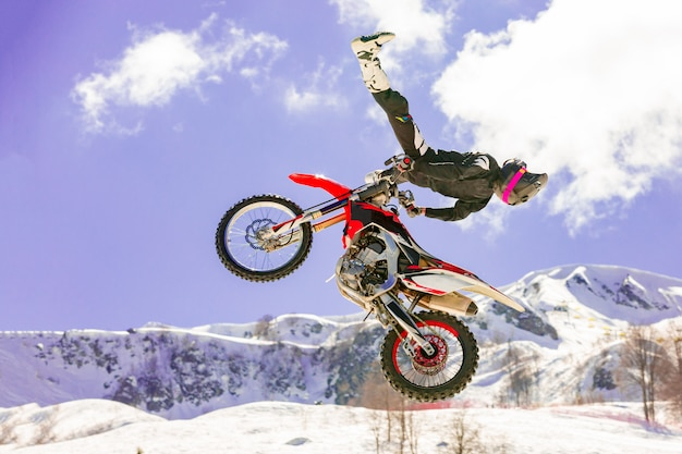 Rennfahrer auf einem motorrad im flug, springt und startet auf einem sprungbrett gegen die schneebedeckten berge