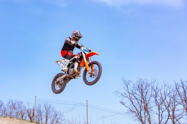 Rennfahrer auf einem motorrad springt und hebt auf einem sprungbrett ab