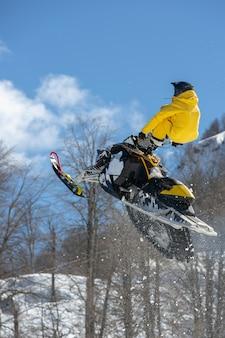 Rennfahrer auf einer schneekatze im flug, springt und hebt auf einem sprungbrett gegen die schneebedeckten berge ab