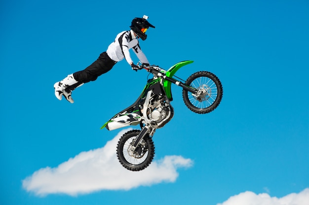 Rennfahrer auf motorrad nimmt am motocross-crosslauf im flug teil