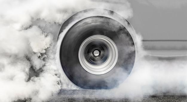 Rennwagen verbrennt gummi von seinen reifen, um sich auf das rennen vorzubereiten