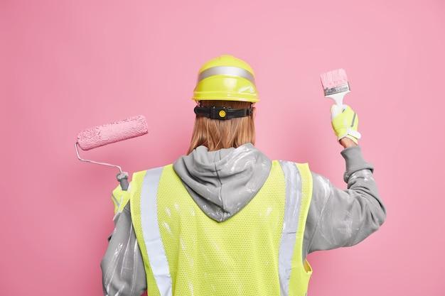 Renovierungsdienstleistungskonzept. rückansicht des rothaarigen mannes verwendet baugeräte, die in arbeitsuniform gekleidet sind und gegen rosa wand posieren. professioneller anstreicher renoviert haus