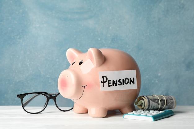 Rentenkonzept. sparschwein, taschenrechner, geld und brille gegen blau, platz für text