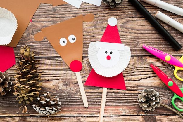 Rentier- und weihnachtsmann-stütze mit papier; tannenzapfen; schere und filzstift auf schreibtisch aus holz