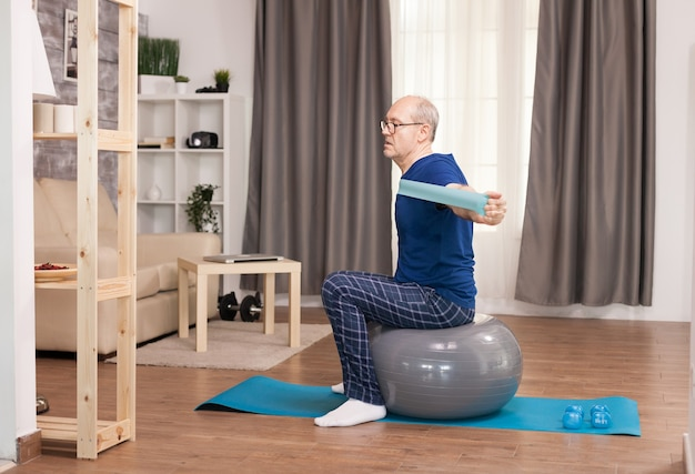 Rentner beim sport mit dem widerstandsband, das auf dem schweizer ball sitzt