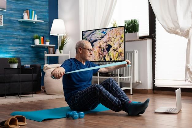 Rentner, der am körperwiderstand arbeitet und die armmuskulatur mit einem gummiband trainiert, das auf einer yogamatte mit gekreuzten beinen sitzt. älterer mann beim training während des fitnesskurses mit blick auf laptop
