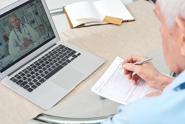 Rentner, der online-video der medizinischen beratung auf laptop-anzeige und ausfüllen des krankenversicherungsformulars ansieht