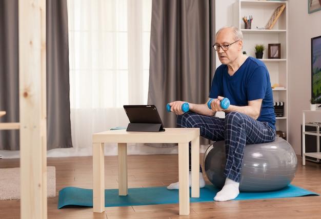 Rentner, der zu hause sport treibt und online-training ansieht