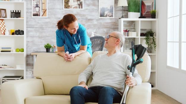 Rentner im pflegeheim im gespräch mit einer krankenschwester. helles zimmer und gute bedingungen