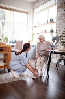 Rentner lächelnd, während pflegekraft schuhe für sie schnürt