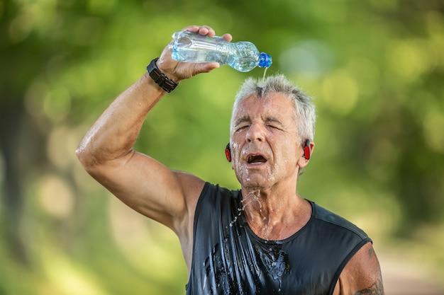 Rentner-läufer kühlt sich ab, indem er frisches wasser aus einer flasche über seinen kopf gießt.