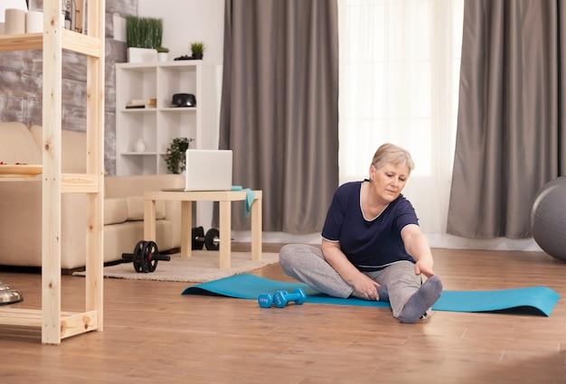 Rentnerfrau, die sich zu hause auf der yogamatte ausdehnt.
