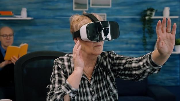 Rentnerin konzentrierte seniorin mit virtual-reality-brille im wohnzimmer und gestikuliert am heimarbeitsplatz. ältere frau, die ein vr-headset erlebt, während ein mann auf dem sofa sitzt und ein buch liest