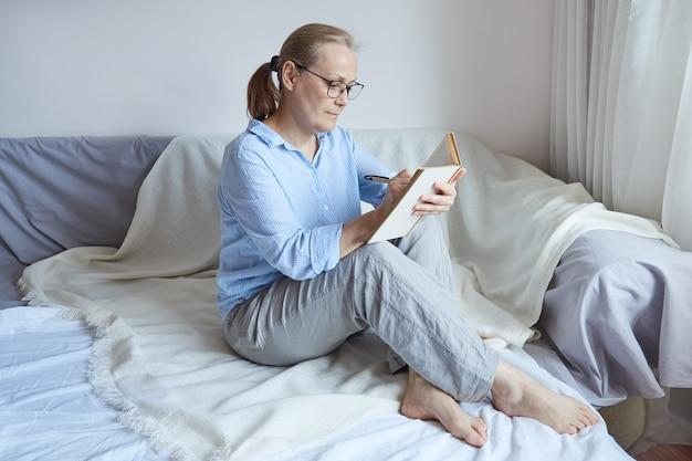 Rentnerin mit brille liest ein buch und macht sich mit einem bleistift notizen, während sie zu hause auf der couch sitzt.